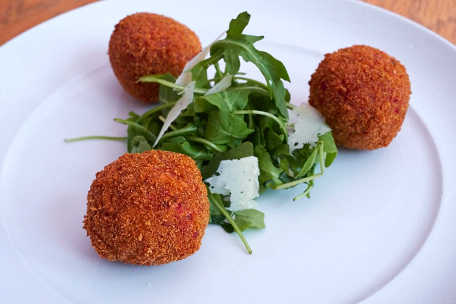Arancini, served with a rocket and parmasan salad